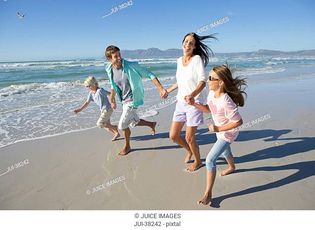 Happy family holding hands and running on sunny beach