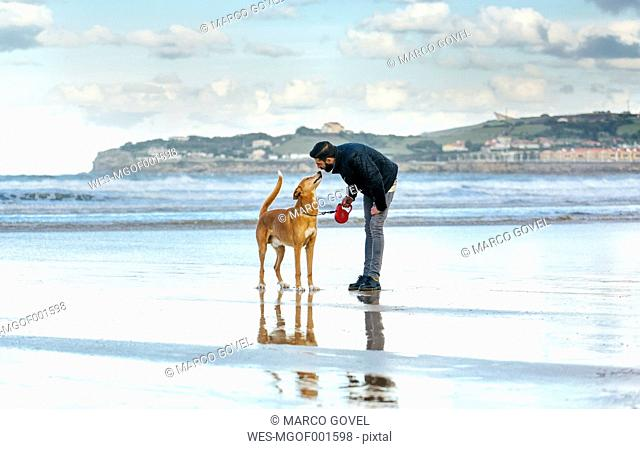 Spain, Gijon, man with his dog on the beach