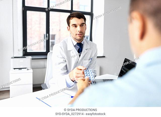 doctor giving medicine to male patient at hospital