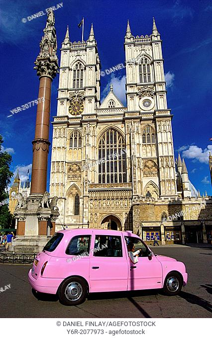 Westminster Abbey in the heart of London, England, with a pink London taxi in the foreground, on a sunny Summer day. Female visitor posing for a picture in the...