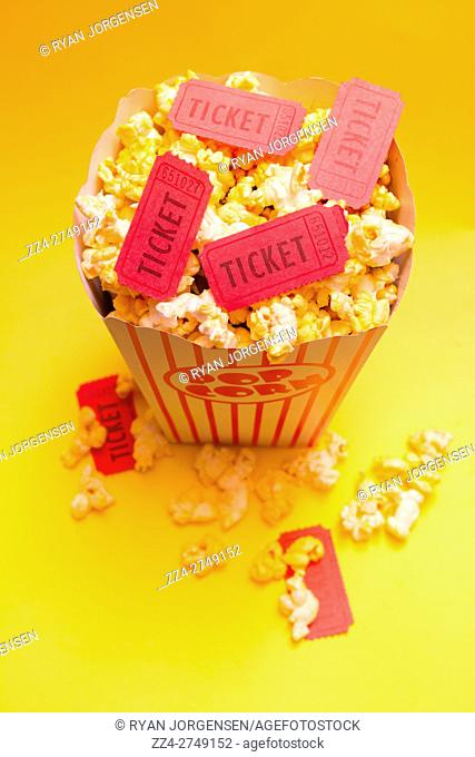 Cinema still life box of butter popcorn in classic container with red movie tickets on top against a retro yellow background