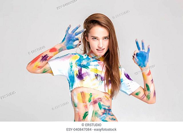 beautiful young woman is dirty in multicolored paint
