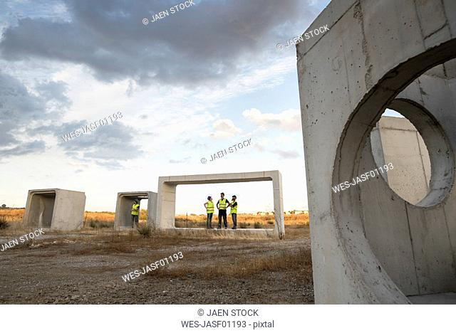 Workers examining concrete structures in rural landscape