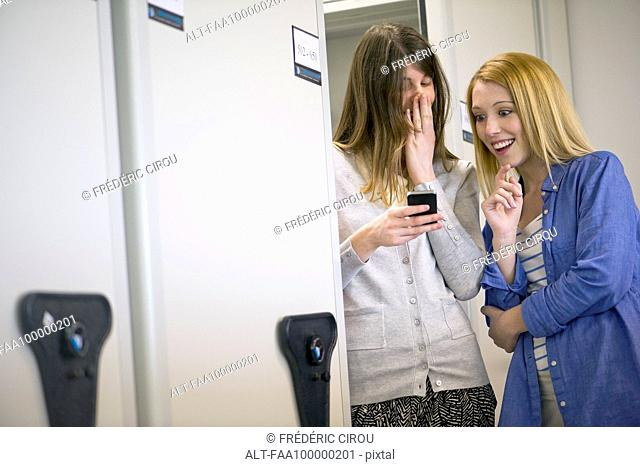 Women laughing at smartphone in office