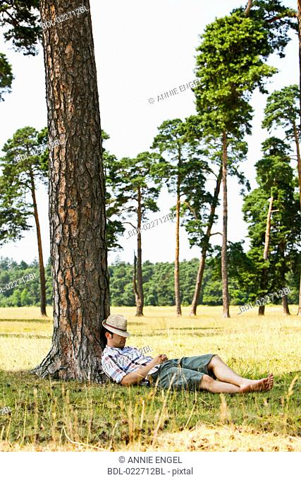 portrait of young man dozing under tree in summer