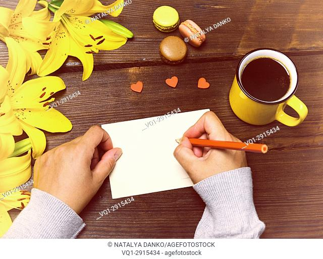 Female hands with a red pencil near a white blank postcard on a brown wooden table, next to a cup of coffee