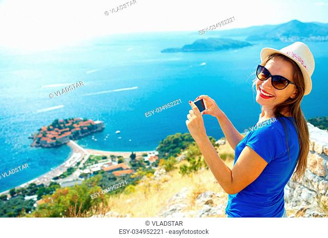 Girl in the hat making photos by the smartphone near the island of Sveti Stefan, Montenegro, Balkans