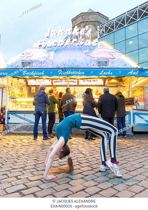 woman exercises urban yoga outdoor at night in front of a fish shop