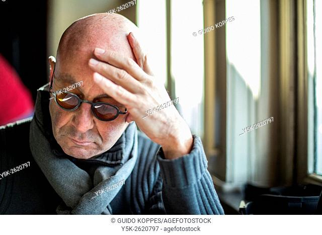Rotterdam, Netherlands. Balding, middle aged man reading the menu of Hotel New York restaurant, while leaning his head on his left hand