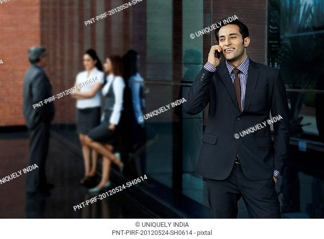 Businessman talking on a mobile phone with their colleagues in the background