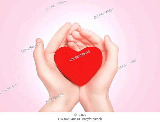 Open hands holding showing red heart over pink background
