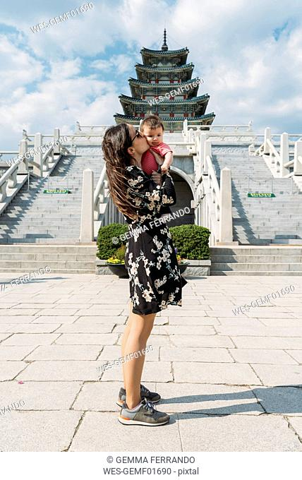 South Korea, Seoul, woman holding and kissing a baby girl in front of the National Folk Museum of Korea, inside Gyeongbokgung Palace