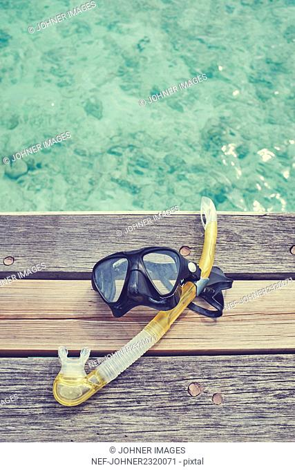 Diving mask and snorkel on wooden pier