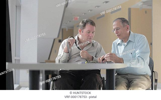 Two Electronics Design Engineers selecting integrated circuit for design, one man quadriplegic in a wheelchair