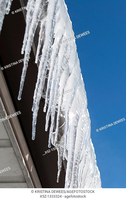 Ice covered gutters against a blue sky in Winter