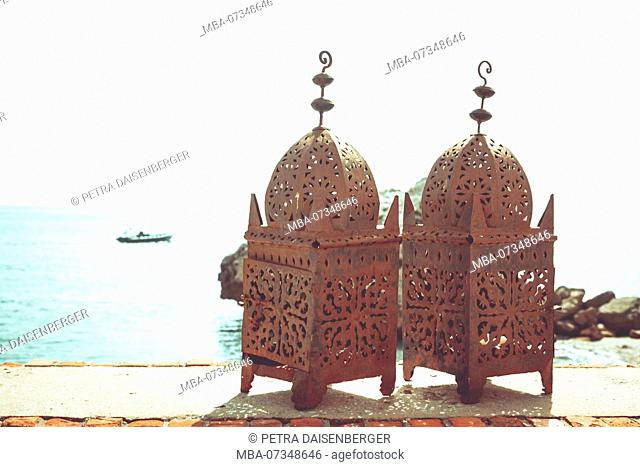 Two rusty Mauritanian lanterns standing on a parapet overlooking the Mediterranean Sea in Gibraltar