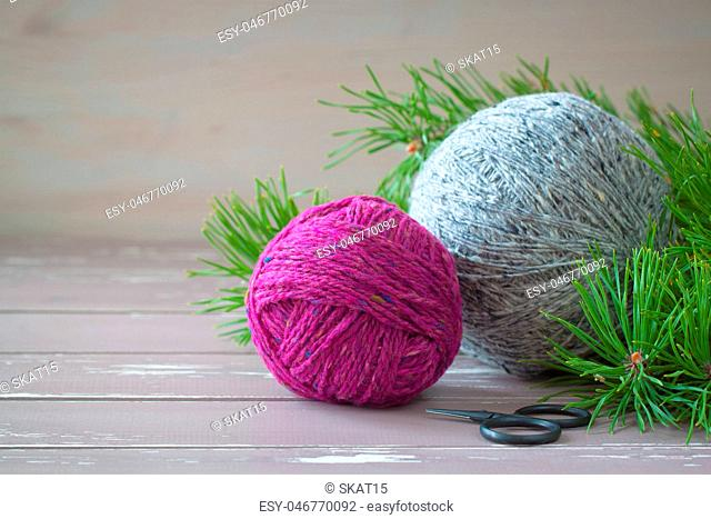 Fuchsia and grey tweed yarn on the wooden background near branches of pine-tree