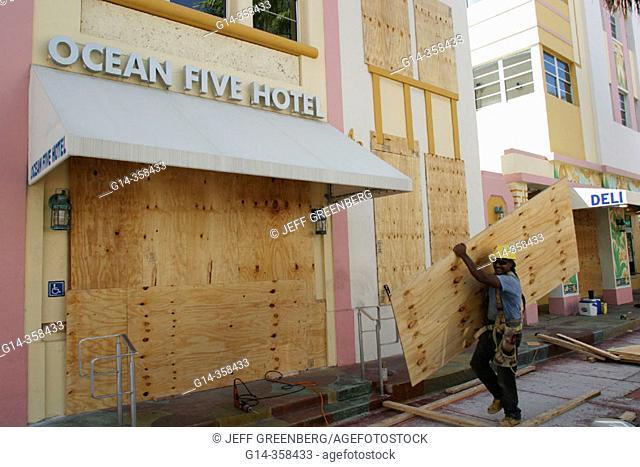 Ocean Five Hotel worker installing plywood hurricane shutters, Hurricane Frances approaching. Ocean Drive, South Beach, Miami Beach. Florida, USA