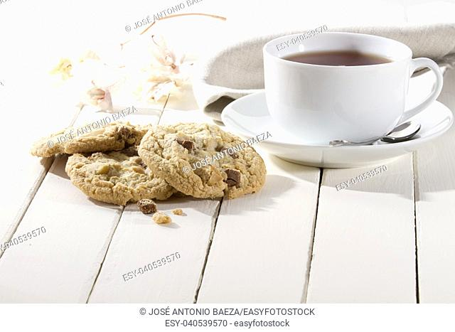 crispy cookies with chocolate and nuts on a white wooden table