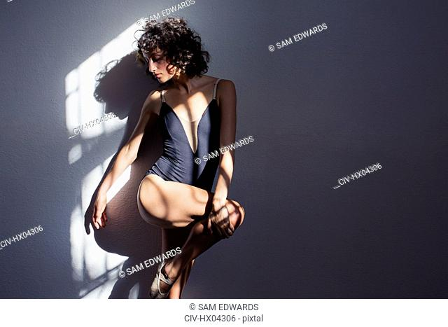 Sensual young female dancer stretching leg in sunlight at wall
