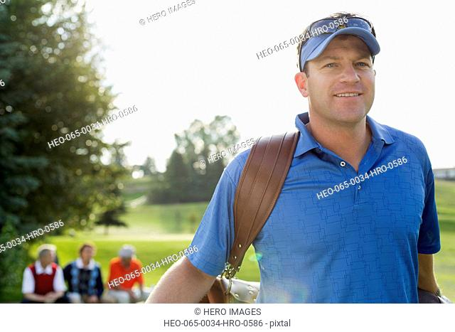 middle-aged golfer walking off tee-box with golf bag