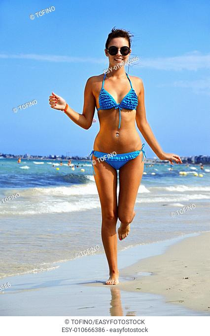 Young woman on the mediterranean beach during hot summer day