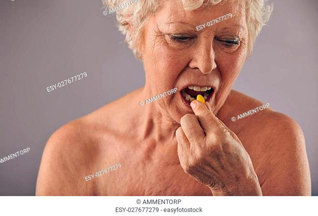 Portrait of senior caucasian woman having a pill against grey background. Naked woman talking medicine