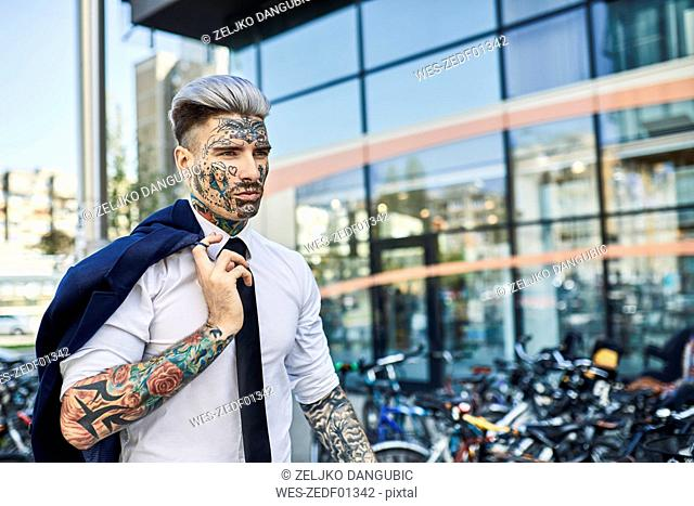 Young businessman with tattooed face walking in the city, portrait