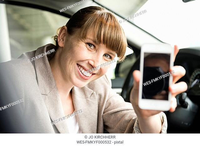 Portrait of smiling businesswoman sitting in a car showing her smartphone
