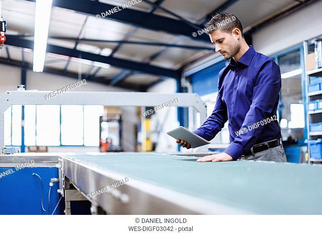 Businessman working in shop floor, using digital tablet