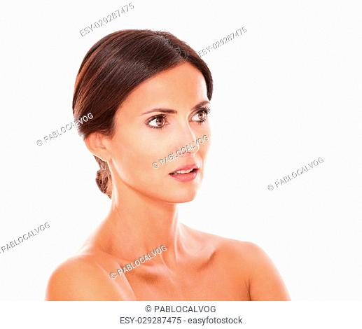 Head and shoulders portrait of pretty hispanic female for facial care product looking to her left with nude shoulders on isolated studio
