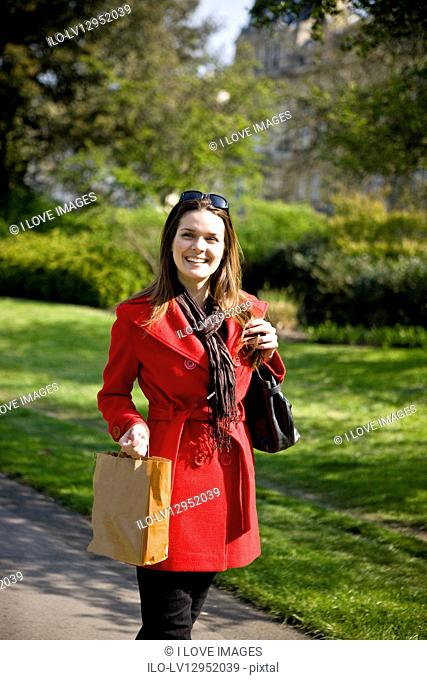 A young woman walking, carrying a shopping bag