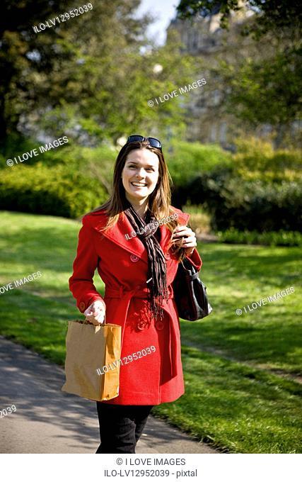 A young woman walking, carrying a shopping bag