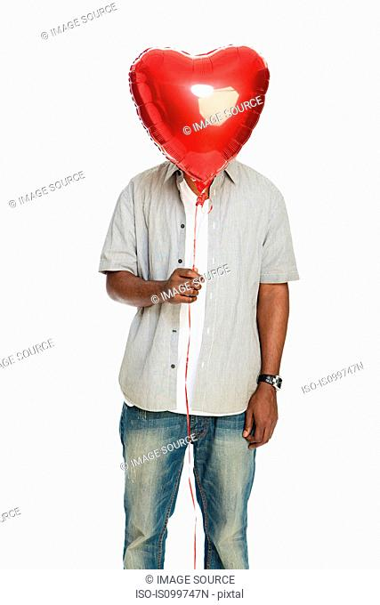Mid adult man holding red balloon against white background