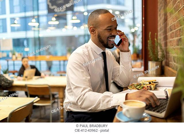 Smiling businessman talking on smart phone, working in cafe