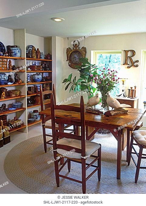 DINING ROOMS: Country charm, 1800's Wisconsin country table with 1940's ladder back chairs, braided rug. Shelving units filled with brown and blue and white...