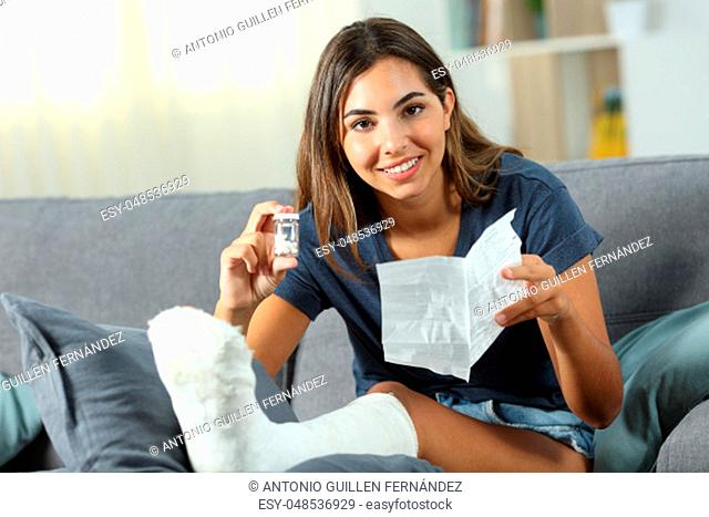 Happy disabled woman showing a bottle of pills sitting on a couch in the living room at home
