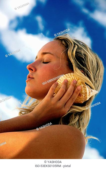 Woman listening to seashells outdoors