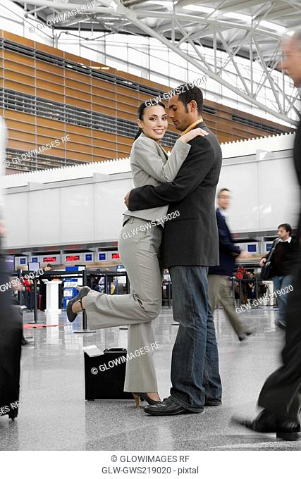 Side profile of a businessman and a businesswoman hugging each other at an airport