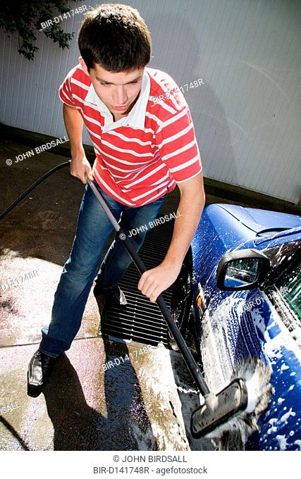 Young Czech man washing car