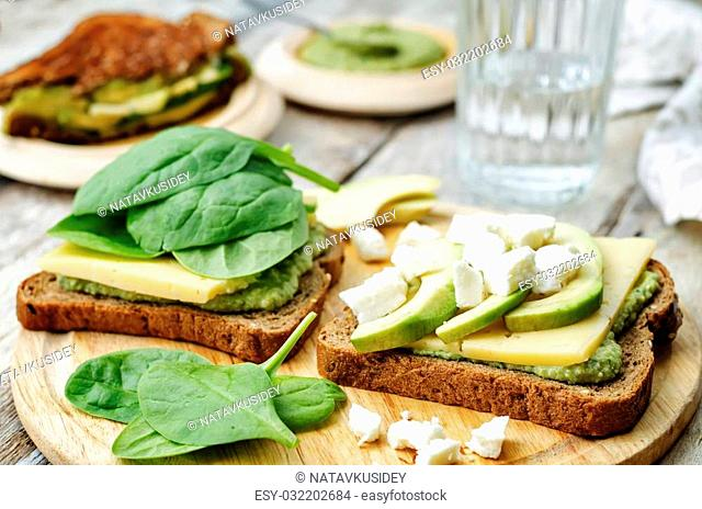 grilled rye sandwiches with cheese, spinach, pesto, avocado and goat cheese. the toning. selective focus