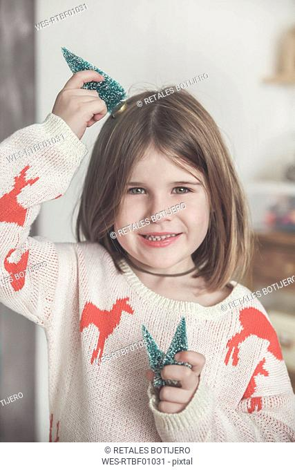 Portrait of smiling little girl with miniature Christmas trees