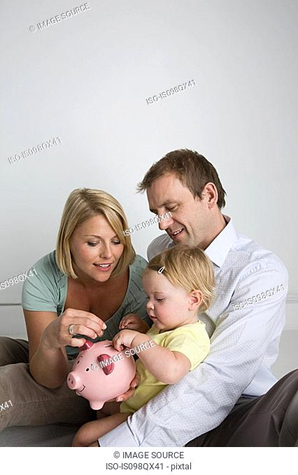 Parents and baby with piggy bank