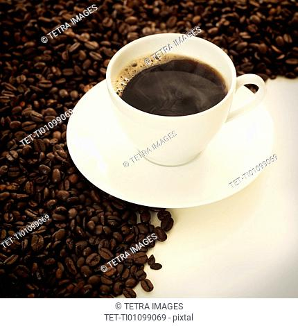 Cup of coffee among coffee beans