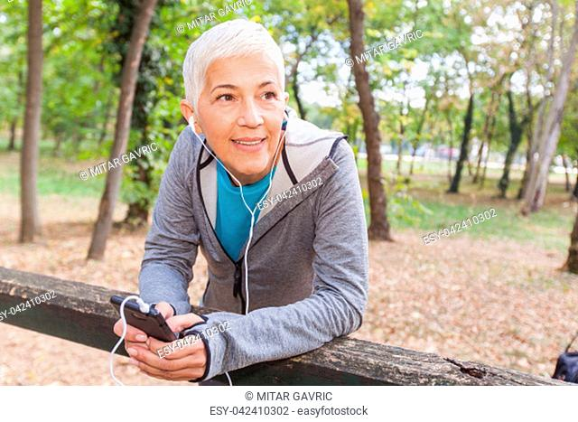 Healthy Senior Woman Relax Listening Music With Phone After Jogging In Forest. Fit Lifestyle Mature People Workout Outdoor
