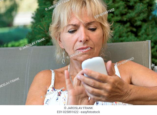 Closeup view of attractive blond senior woman is learning to use her smart phone, which is holding in her hand. All potential trademarks are removed