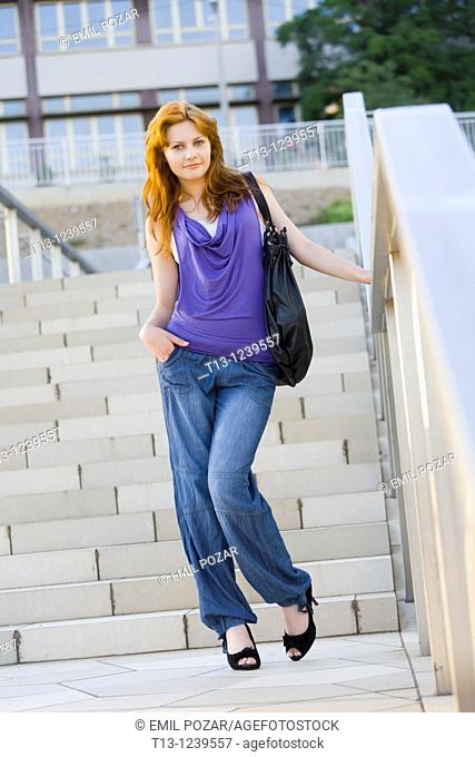 Young woman is posing before staircase