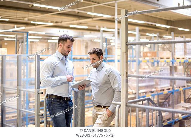 Two men in factory warehouse looking at tablet
