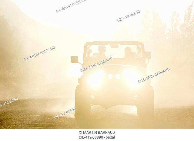 Sport utility vehicle driving on dirt road