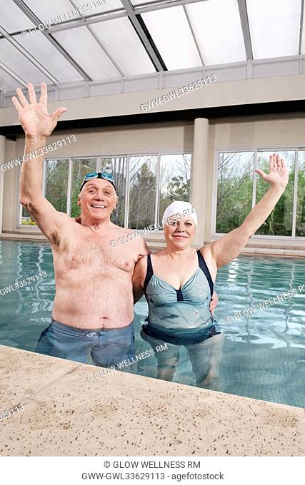 Couple smiling in a swimming pool with their hands raised